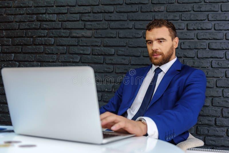Eleganter Geschäftsmann in der Klage, die zuhause arbeitet stockbild