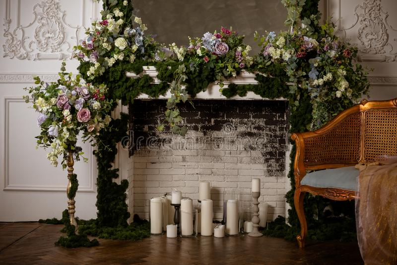 Eleganter grauer Ziegelsteinkamin voll von Blumen und von Kerzen Eleganter Raum Heiratsverzierter Bereich Weinlesedekorinnenraum stockfotografie