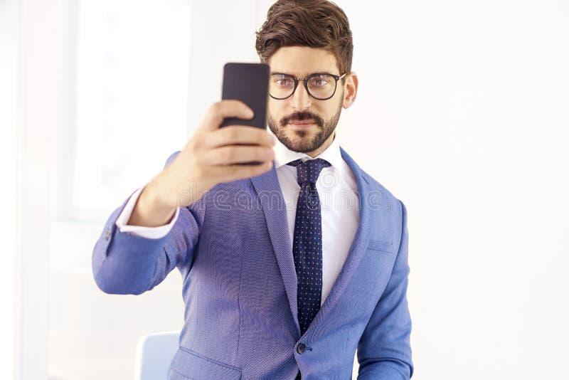 Eleganter hübscher Geschäftsmann, der Selbstporträt beim Sitzen nimmt lizenzfreie stockfotos