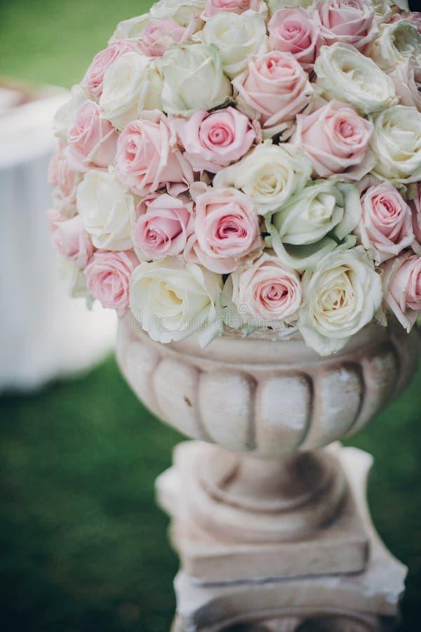 Eleganter Heiratsblumenstrauß auf Spalte, stilvoller Dekor des Heiratsganges draußen Anordnung der Rosa- und weißerrosen am Hochz lizenzfreies stockbild