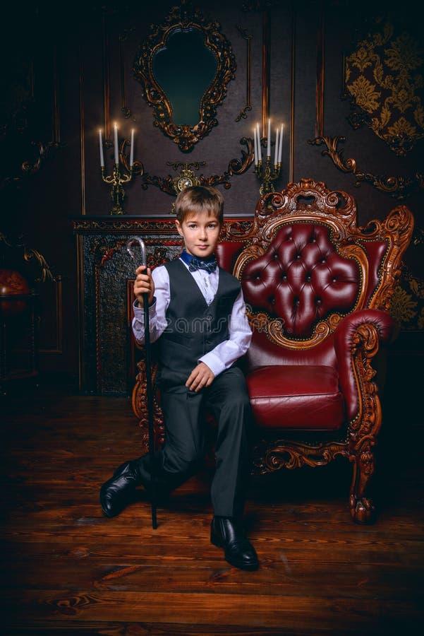 Eleganter Junge im Lehnsessel stockbild