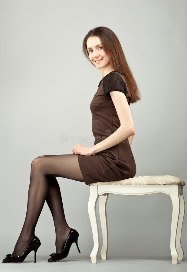 Eleganter junger Brunette, der auf einem Banquette sitzt stockfotos
