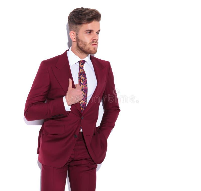 Eleganter junger Geschäftsmann, der Kragen hält und weg schaut lizenzfreies stockbild