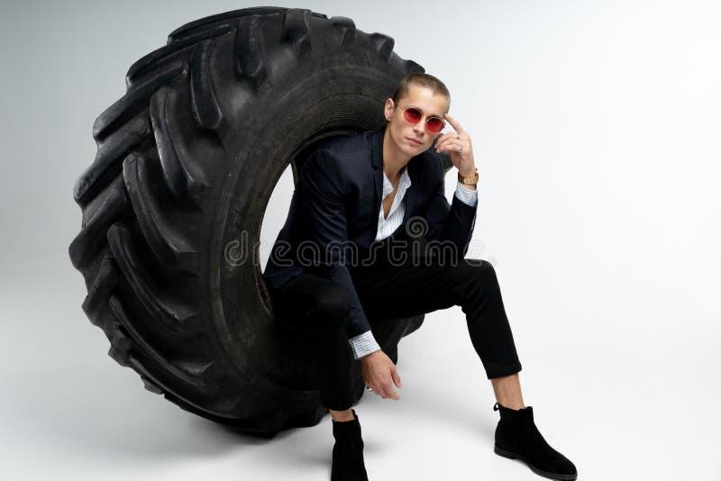 Eleganter junger Gesch?ftsmann im schwarzen Anzug und roten in der Sonnenbrille, die im gro?en Reifen, die Kamera betrachtend sit lizenzfreies stockfoto