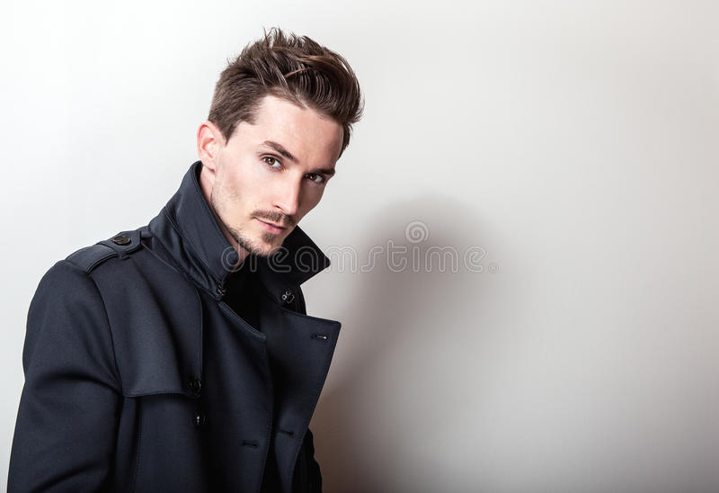 Eleganter junger gutaussehender Mann im langen stilvollen dunkelblauen Mantel Mann entfernen irgendjemandes Kleidung lizenzfreie stockfotos