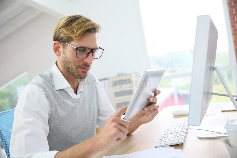 Eleganter junger Mann im Büro, das an Tablette arbeitet stockbilder