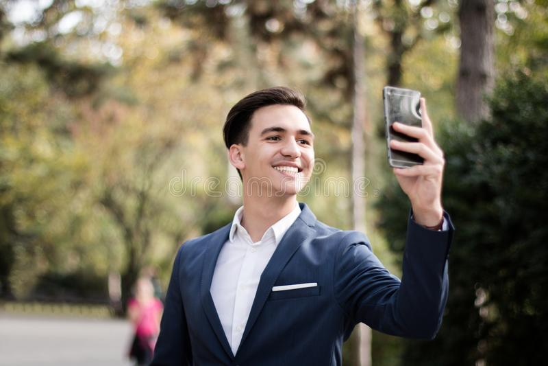 Eleganter junger Mann mit Smartphone im Park stockfotos