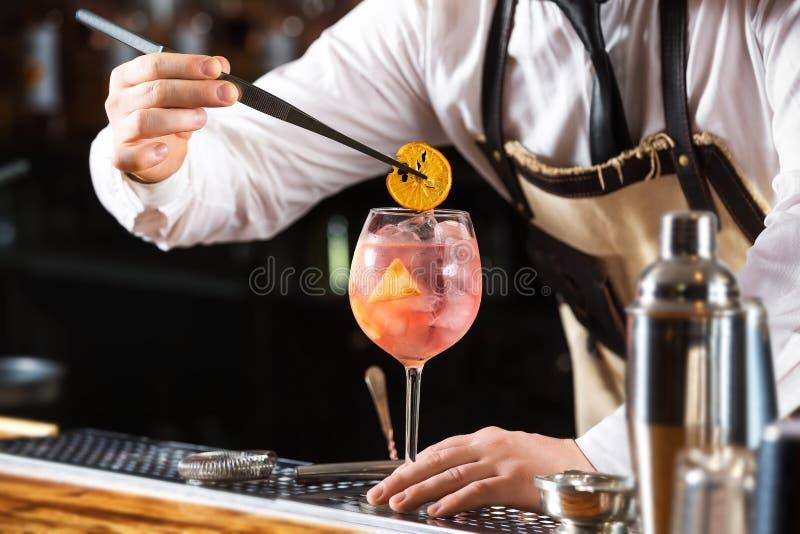 Eleganter Kellner macht das rosa Cocktail, das orange Chips hält stockbild