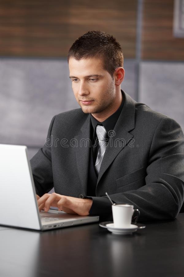 Eleganter Manager, der an Laptop arbeitet lizenzfreie stockbilder