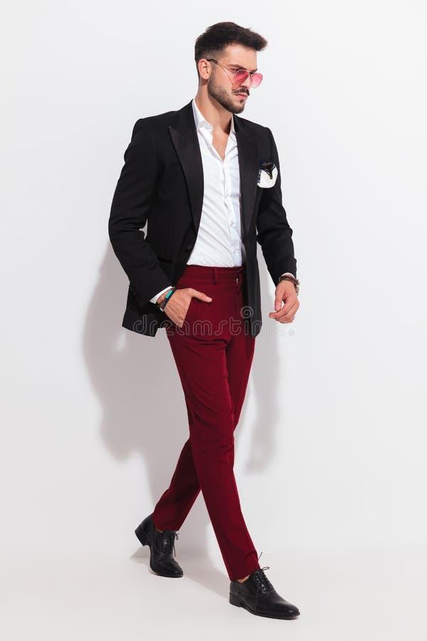 Eleganter Mann, der den schwarzen Anzug geht mit der Hand in der Tasche trägt lizenzfreies stockfoto