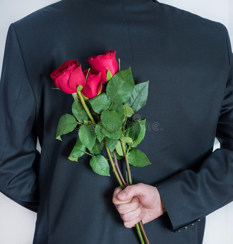 Eleganter Mann, der in der Hand rote rosafarbene Blumen hinter seiner Rückseite hält stockbilder