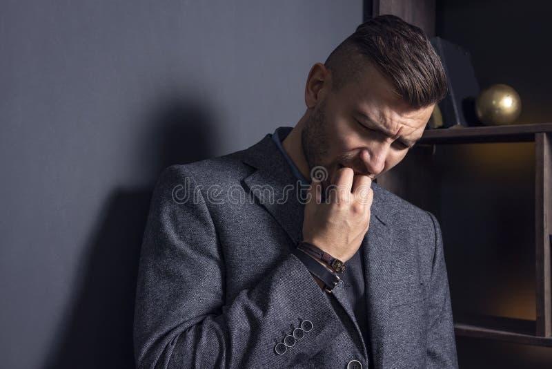 Eleganter Mann ist umgekippt Hoffnungsloser Mann ist nervös Niedergedrückter Kerl in einem Anzug Geschäfts-Frustration stockfoto