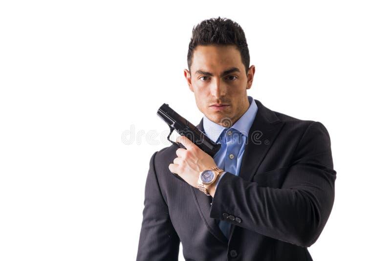 Eleganter Mann mit dem Gewehr, gekleidet als Spion oder Geheimagent stockfoto