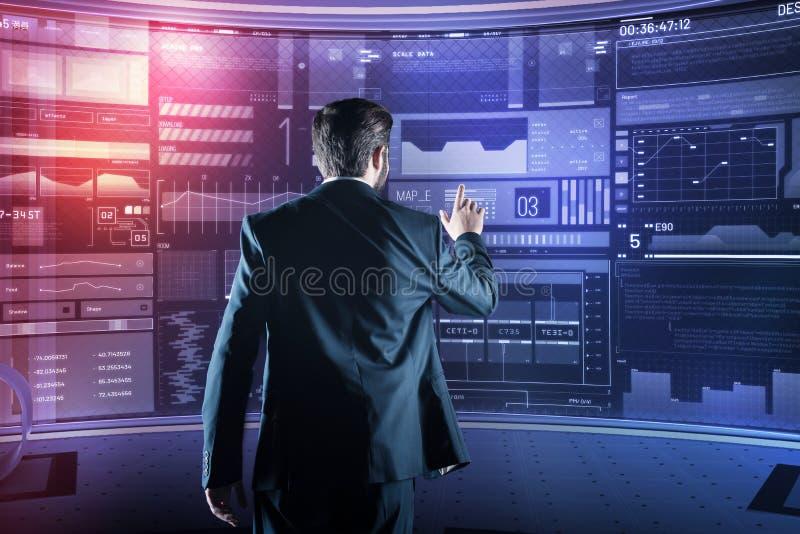 Eleganter Programmierer, der auf den Schirm beim Arbeiten in seinem futuristischen Büro zeigt lizenzfreies stockfoto
