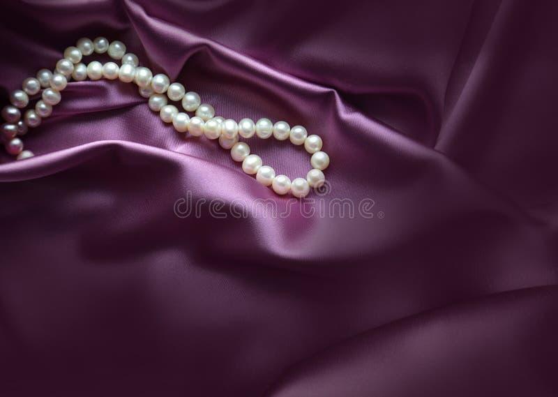 Eleganter purpurroter Hintergrund mit Seide und Perlen stockfoto