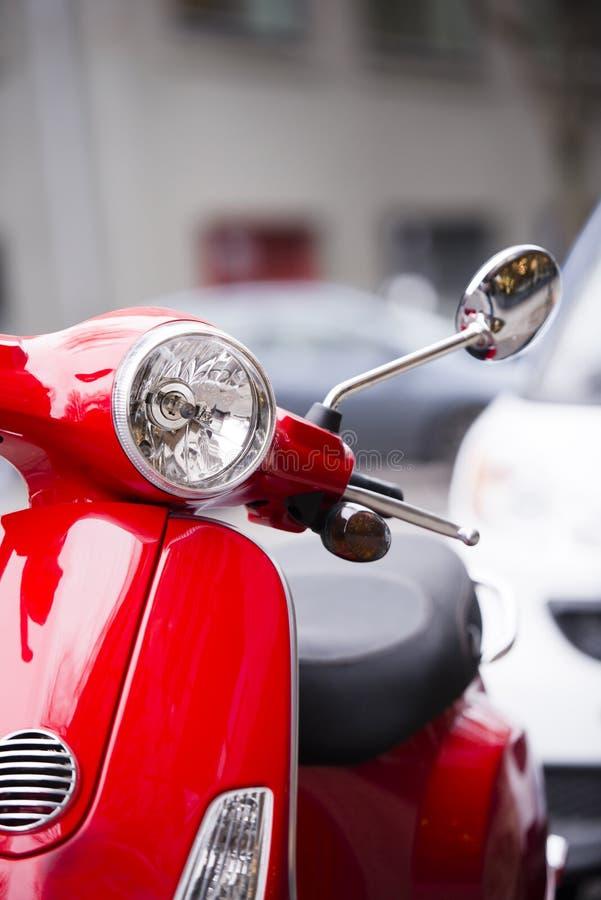 Eleganter roter Roller eingeladen, um auf städtische Stadtstraßen zu fahren lizenzfreies stockfoto
