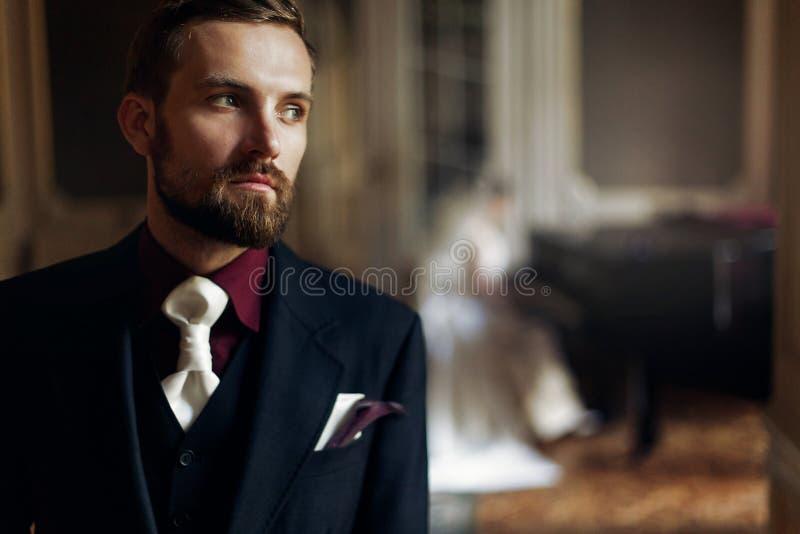 Eleganter stilvoller hübscher Bräutigam, der auf seine herrliche Braut p hört stockfotografie