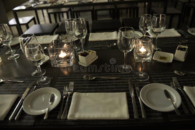 Eleganter Tabellen-Satz, brennende Kerzen, Weiß faltete Serviette - modernes Restaurant lizenzfreie stockfotografie