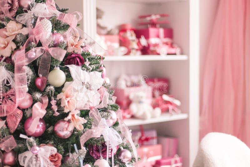 Eleganter Weihnachtsbaum verziert mit Spielwarenbällen und -bändern in einem hellen Innenraum Weicher Fokus lizenzfreie stockbilder