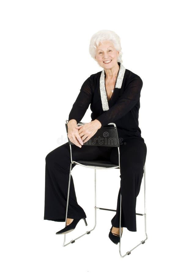Elegantes älteres Frauensitzen lizenzfreies stockbild