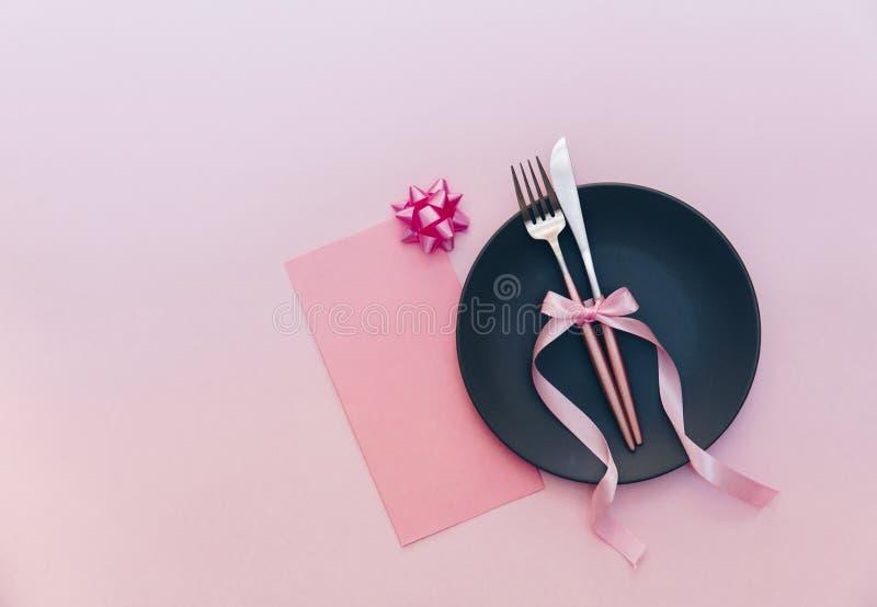 Elegantes Feiertagstabellengedeck mit Karten- und Tischbestecknahaufnahme auf Rosa lizenzfreies stockbild