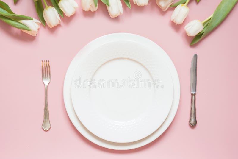 Elegantes Gedeck mit weißer Tulpe auf rosa Tabelle r stockfotos