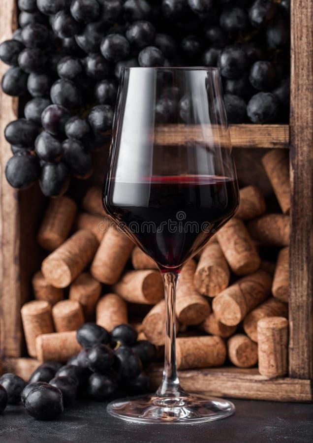 Elegantes Glas Rotwein mit dunklen Trauben und Korken innerhalb der Weinleseholzkiste auf schwarzem Steinhintergrund Nat?rliche L stockfoto