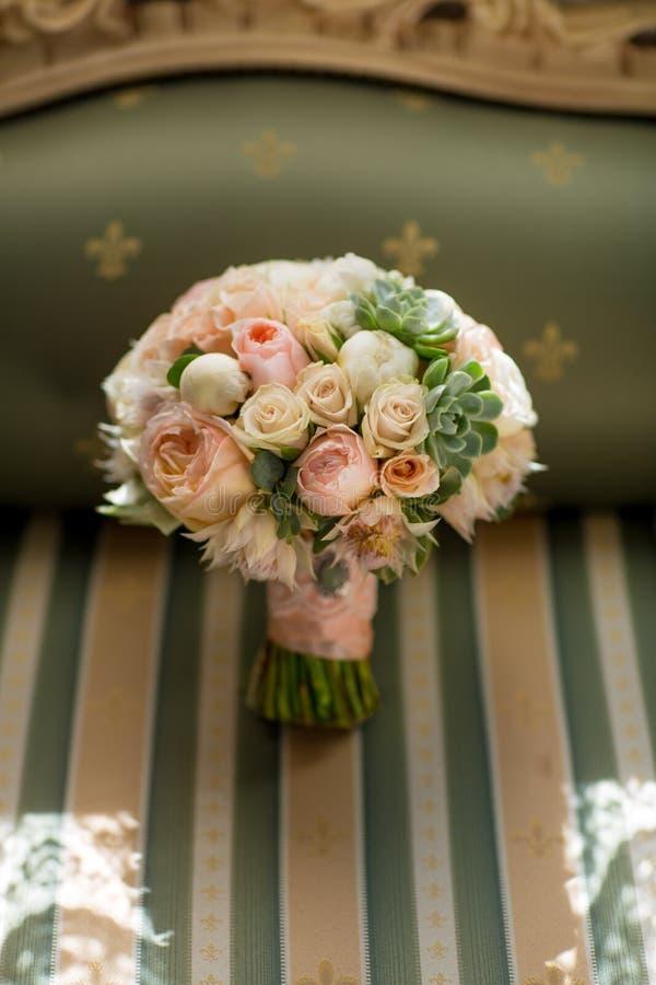 Elegantes Hochzeitsblume bouqet auf Beschaffenheitsgrünsofa stockfotografie