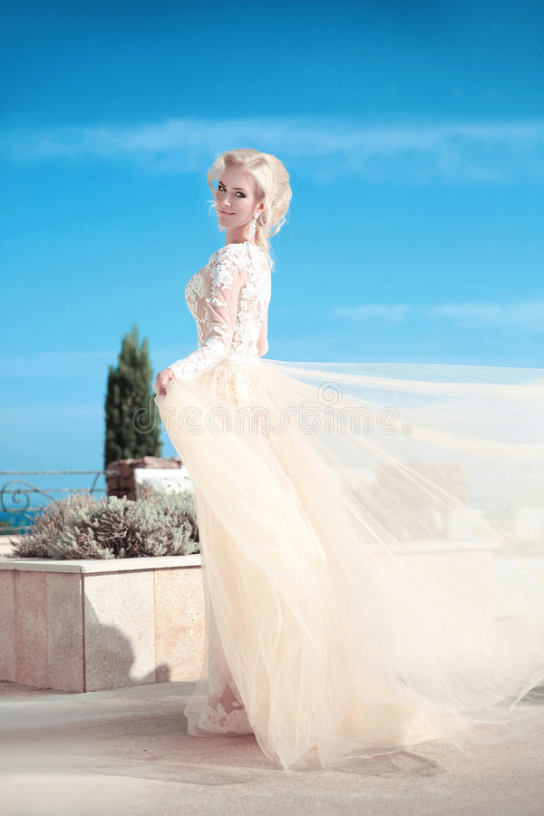 Elegantes Hochzeitskleid der Brautfrau in Mode über blauem Himmel Attr stockbild