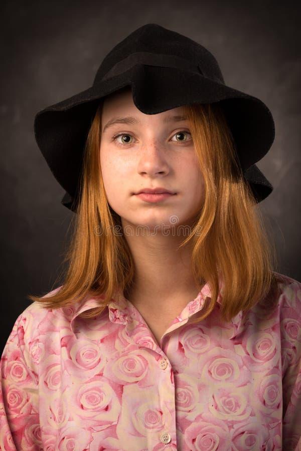 Elegantes jugendlich Mädchen, das schwarzen Hut auf dunklem Hintergrund trägt Jugendmode lizenzfreie stockfotos