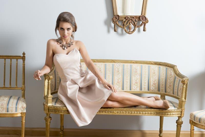 Elegantes Mädchen, das auf Weinlesesofa liegt stockfotos