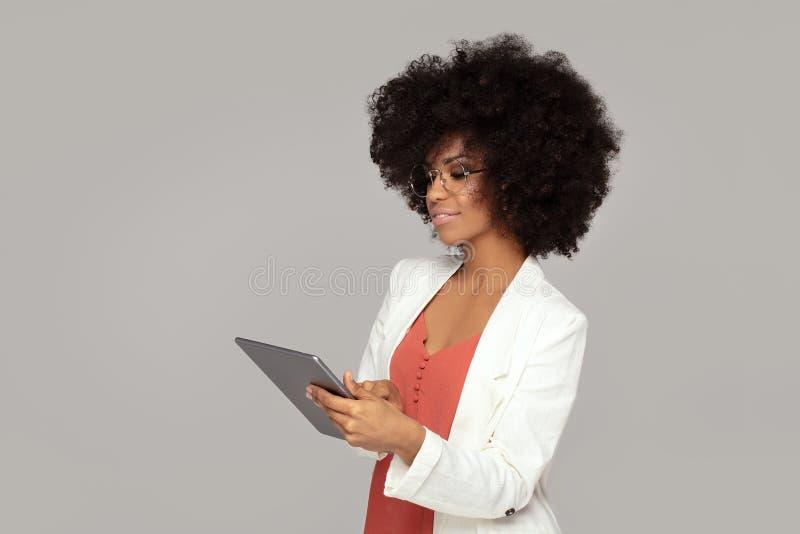 Elegantes Mädchen des Afro, das Tablette verwendet lizenzfreie stockbilder