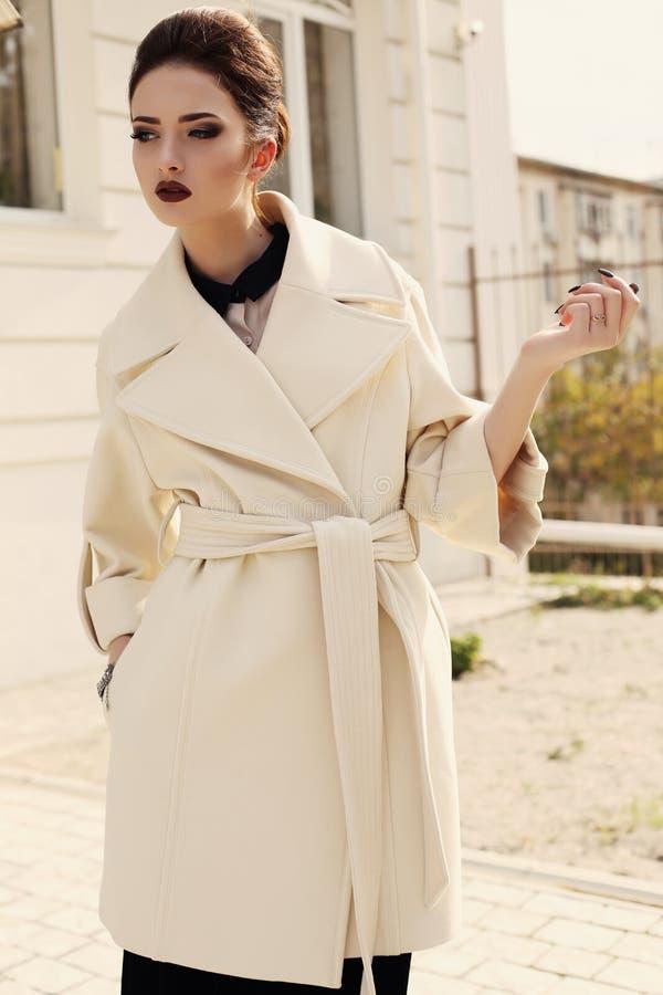 Elegantes Mädchen mit dem dunklen Haar, das luxuriösen beige Mantel trägt stockfotos