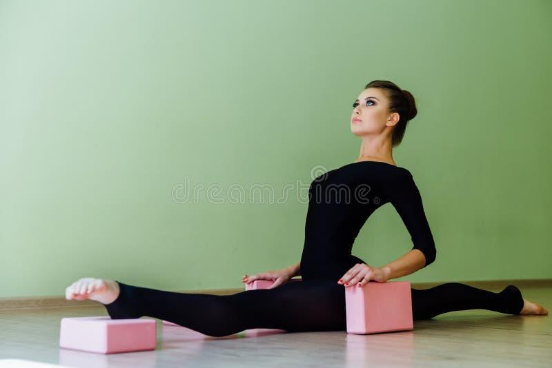 Elegantes schönes Tänzermädchen des modernen Balletts mit perfektem Körper sitzt auf dem Boden an auf Schnur stockbilder