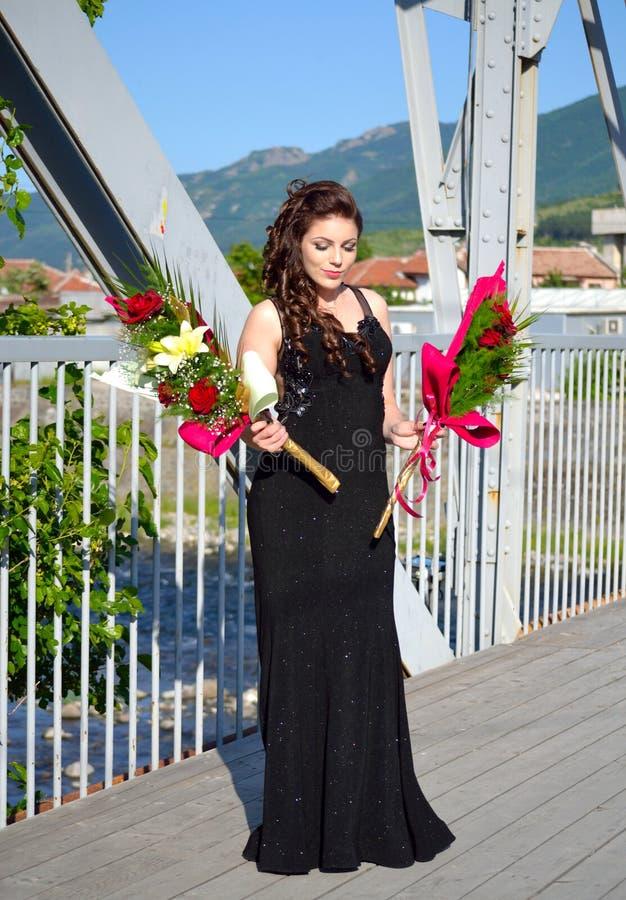 Elegantes Schönheitsabschlussballmädchen mit Blumen Bulgarien lizenzfreie stockfotografie