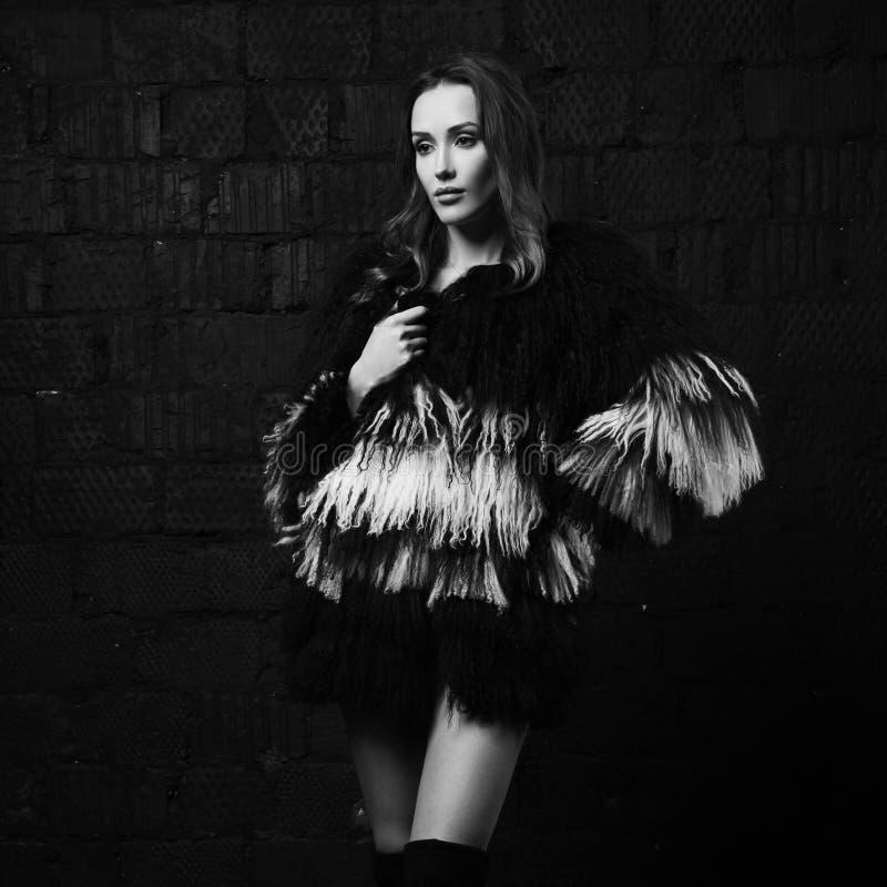 Elegantes weibliches Modell im Fauxpelzmantel, der gegen grauen Ziegelstein aufwirft lizenzfreie stockbilder