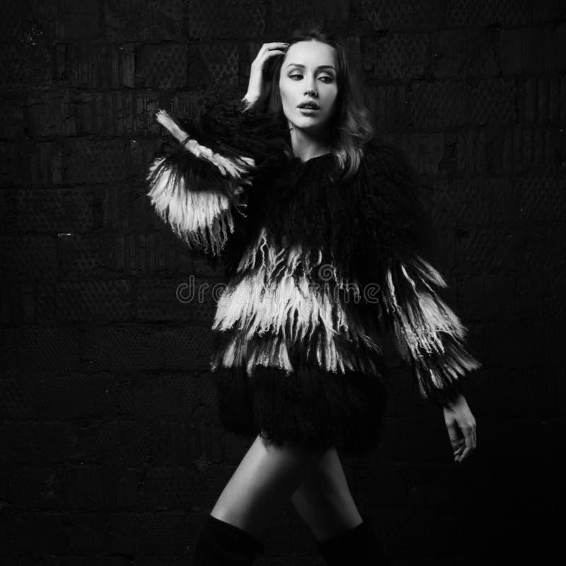 Elegantes weibliches Modell im Fauxpelzmantel, der gegen grauen Ziegelstein aufwirft stockbild