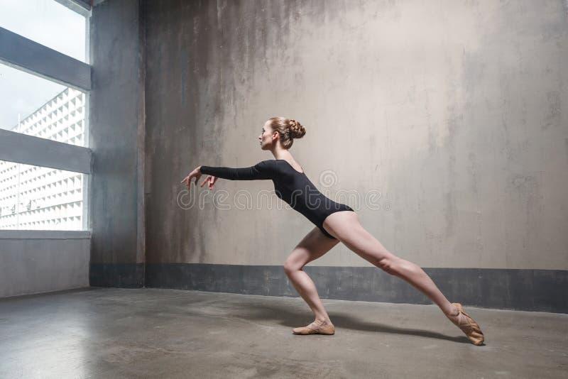 Elegantie slanke vrouw die dichtbij het venster dansen stock foto's