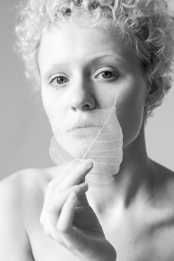 Elegantiemeisje met een droog in hand blad, zwart-witte foto stock afbeeldingen