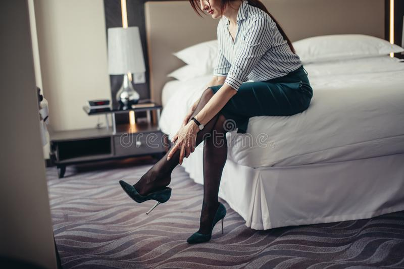 Business lady being tired after a long journey resting on bed in hotel room. Elegantly dressed business woman, relaxing on hotel room bed after a long business stock photos