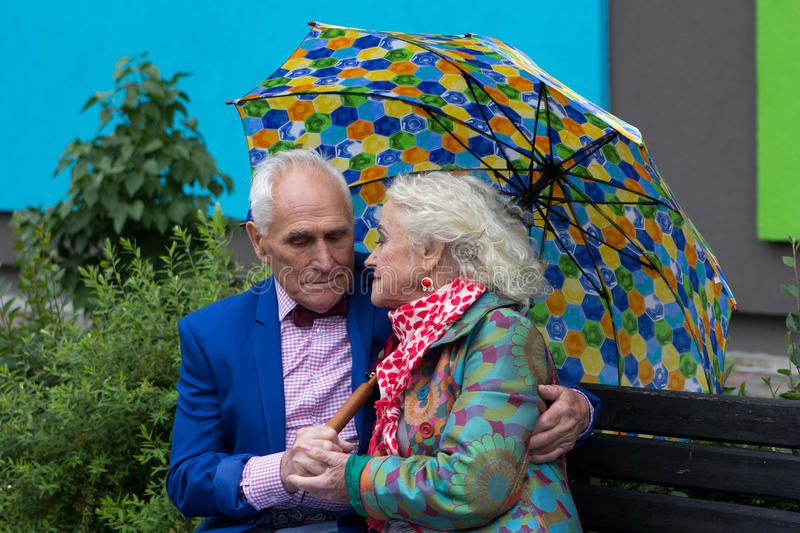 Elegantly dressed elderly couple sitting on a bench. Elegantly dressed elderly couple sitting on a bench under an umbrella royalty free stock photos