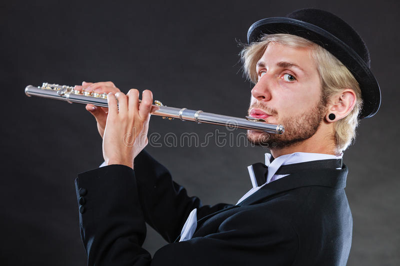 Elegantly dressed male musician playing flute. Classical music, passion and hobby concept. Elegantly dressed musician man playing on flute wearing black fedora royalty free stock image