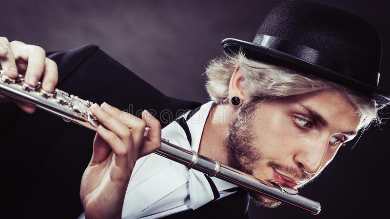 Elegantly dressed male musician playing flute. Classical music, passion and hobby concept. Elegantly dressed musician man playing on flute wearing black fedora royalty free stock images