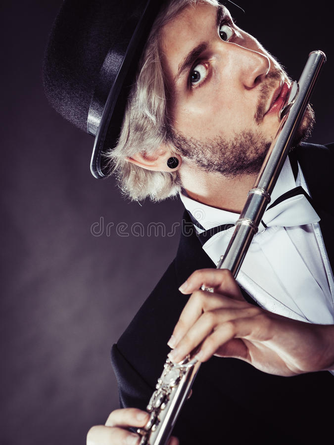 Elegantly dressed male musician playing flute. Classical music, passion and hobby concept. Elegantly dressed musician man playing on flute wearing black fedora stock photo
