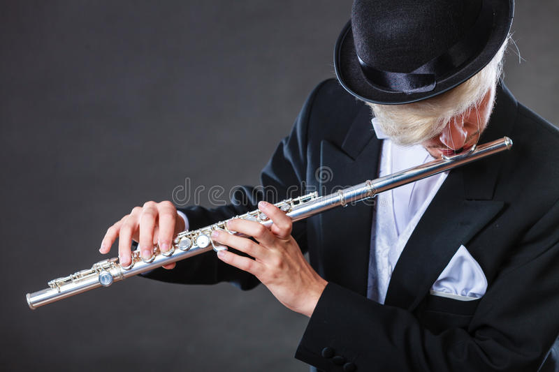 Elegantly dressed male musician playing flute. Classical music, passion and hobby concept. Elegantly dressed musician man playing on flute wearing black fedora royalty free stock photos