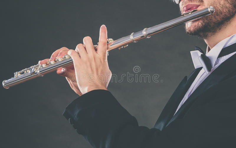 Elegantly dressed male musician playing flute. Classical music, passion and hobby concept. Elegantly dressed musician man playing on flute wearing black fedora royalty free stock photo