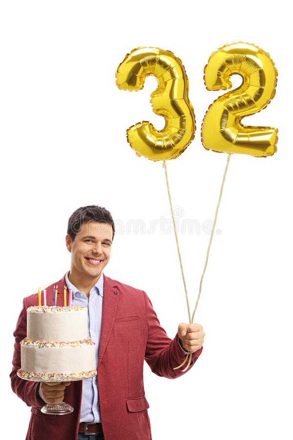 Elegantly dressed man holding a birthday cake and a number thirty-two shaped balloon. Isolated on white background royalty free stock photography