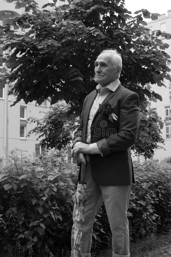 Elegantly dressed old man standing outdoors alone. Black and white. stock photo