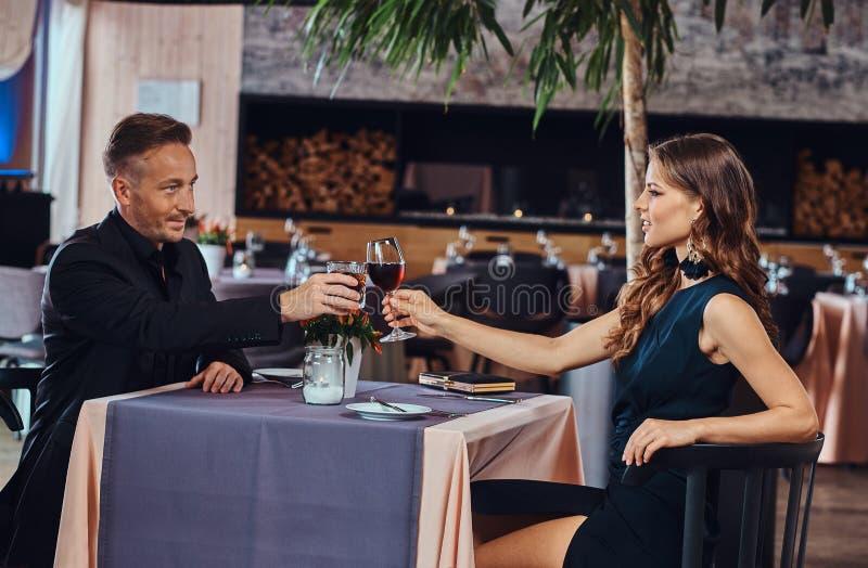 Elegantly påkläddpar - en attraktiv man och hans charmiga kvinna som klirrar med vinexponeringsglas i den lyxiga restaurangen royaltyfri fotografi