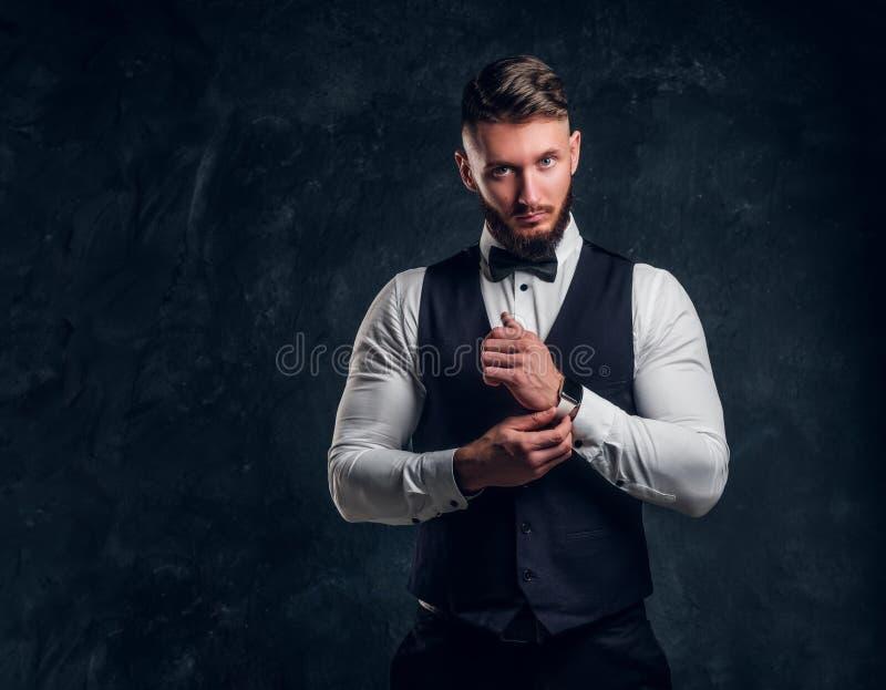 Elegantly skäggig hipster för påklädd i en väst med flugan Studiofoto mot en mörk väggbakgrund arkivbild